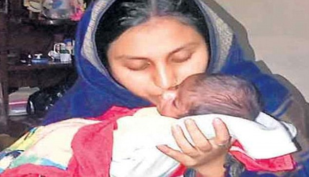 Reunited: Mother Noora kisses her 10-day-old baby who was sold to a child trafficking ring by his own grandfather when he was just three days old.